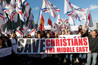 Assyrian Christians, who had fled Syria and Iraq, carry placards and wave Assyrian flags during a gathering in late May in front of U.N. headquarters in Beirut.