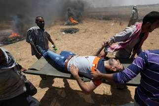 A wounded Palestinian is evacuated at the Israel-Gaza border during a protest against the U.S. embassy move to Jerusalem May 14.