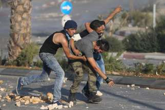 A wounded Palestinian protester is evacuated during clashes with Israeli troops near Ramallah, West Bank, Oct. 16.  The Palestinian Authority has asked municipalities to tone down their public Christmas celebrations this year amid escalating violence between Palestinians and Israelis.