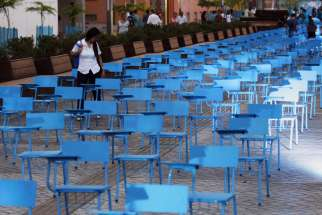 A girl walks among a blue chairs installation for Human Trafficking Awareness Day in Cali, Colombia, July 30. The chair represent more than 20 million men, women and children who are victims of human trafficking worldwide.