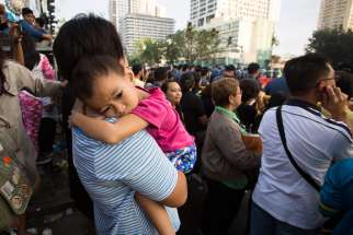A mother holds her sick daughter in Manila, Philippines, Jan. 19, while waiting for Pope Francis to commute to the airport and return to Rome.