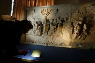 A journalist looks at a replica of the 1st-century Arch of Titus, showing Roman soldiers carrying the menorah, in a exhibition at the Vatican May 15. The replica is the central motif in a two-part exhibition on the menorah at the Vatican and at the Jewish Museum in Rome.