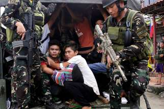 Filipino residents of Marawi are escorted to safety by government forces June 3.The Association of Major Religious Superiors in the Philippines called for an end to martial law in Mindanao, saying it was not the proper response to terrorist attacks in one city on a vast island.