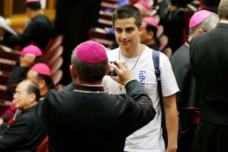 A bishop takes a photo of a youth delegate before the opening session of the Synod of Bishops on young people, the faith and vocational discernment at the Vatican Oct 3.