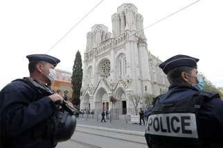 Police stand near Notre Dame Basilica in Nice, France, Oct. 29, 2020, after at least three people were killed in a series of stabbings before Mass. France raised its alert level to maximum after the attack.