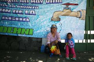 A woman and child sit in front of water poster in San Salvador, El Salvador, July 24, 2017
