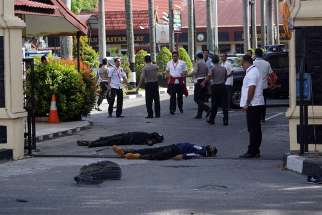 The bodies of two attackers who were shot and killed May 16 are seen at the entrance of a police station in Pekanbaru, Indonesia.