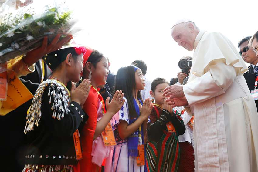 Pope Francis greets children as he arrives at Yangon International Airport in Yangon, Myanmar, Nov. 27. The pope is making a six-day visit to Myanmar and Bangladesh.