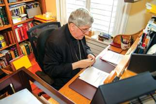 Cardinal Thomas Collins goes over the large collection of paperwork that accumulates throughout the day.