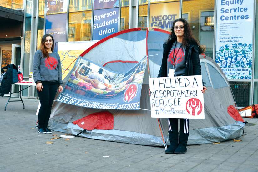Nina Moshy, left, and Rosemary Yachouh stand in front of the Ryerson Student Centre to spread awareness about the plight of Syrian refugees.