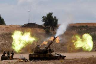 An Israeli mobile artillery unit fires toward the Gaza Strip July 18. Pope Francis telephoned Israeli President Shimon Peres and Palestinian President Mahmoud Abbas July 18, urging all sides to end hostilities and build peace.