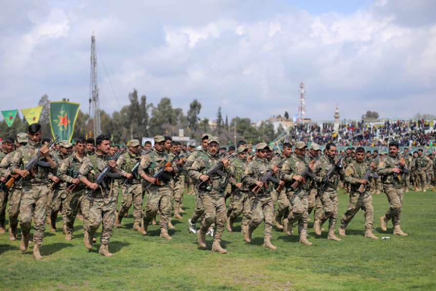 Kurdish fighters in Qamishli, Syria, take part in a military parade March 28, 2019. Groups representing Syriac Christians in northeast Syria are appealing for prayer, fearful that Turkey plans to make good its numerous threats to invade the region with its military forces.