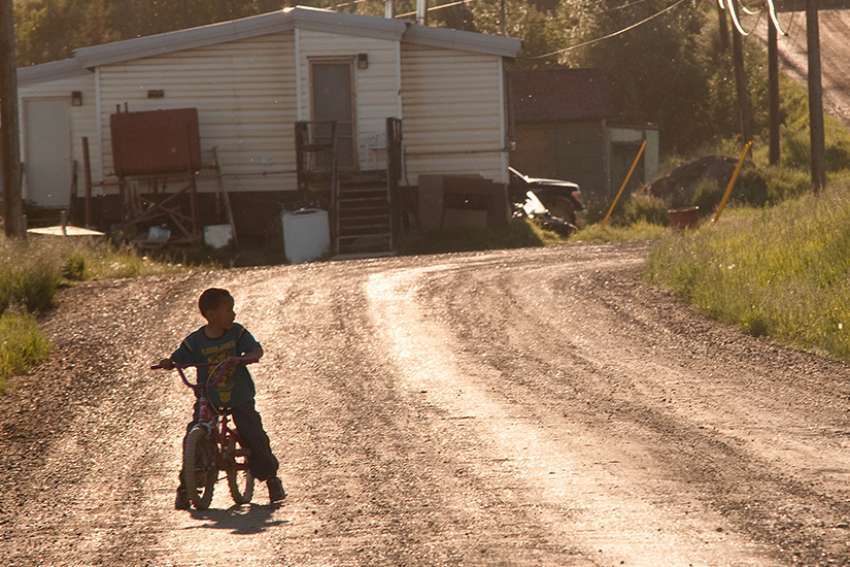 A young boy rides his bike around his neighbourhood in the reserve.