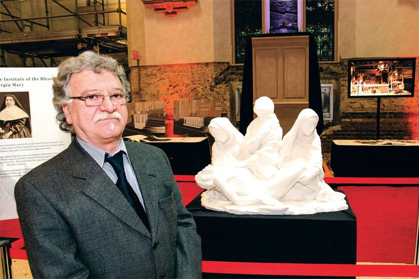 Lawrence Voaides, a master stone carver, next to the one-quarter scale model of his custom Pieta for St. Michael's Cathedral during the cathedral's recent open house