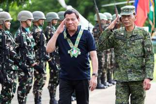 Philippine President Rodrigo Duterte is seen with the military in Carmen, Philippines, June 6. The Association of Major Religious Superiors in the Philippines called for an end to martial law in Mindanao, saying it was not the proper response to terrorist attacks in one city on a vast island.