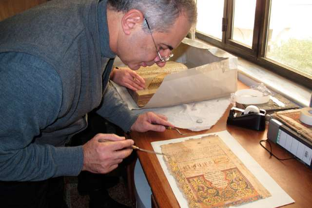 Dominican Father Najeeb Michaeel works on a manuscript at his restoration laboratory in Qaraqosh, Iraq, prior to Aug. 6. Father Michaeel and his team moved 1,300 manuscripts dating from the 14th to 19th centuries before Islamic State militants invaded Qa raqosh Aug. 6.