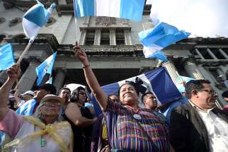 Nobel Peace Prize winner Rigoberta Menchu holds a Guatemalan flag as she joins an Aug. 28 protest against President Jimmy Morales in front of the National Palace in Guatemala City. The Guatemala bishops have criticized the president for trying to oust the internationally appointed commissioner against corruption and impunity.