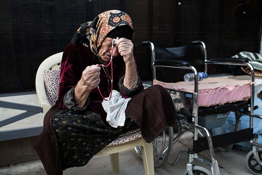 A displaced Iraqi woman prays the rosary in 2014 inside St. Joseph Church in Irbil, Iraq. The church gave refuge to thousands of people who were displaced by the Islamic State.