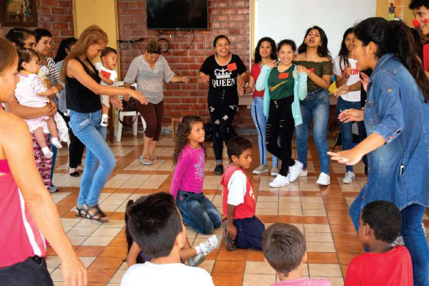 Venezuelan migrants dance during a Christmas event Dec. 16 at the Scalabrini welcome centre in Lima, Peru. A local parish organized the event for migrants living at the centre.