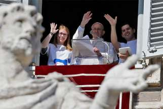 Pope Francis waves after registering for Panama's World Youth Day 2019 during the Angelus prayer in St. Peter's Square Feb. 11 at the Vatican.