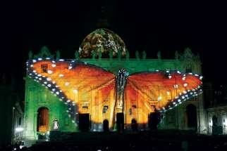 A butterfly is seen in a light show on the facade and dome of St. Peter's Basilica at the Vatican Dec. 8. The show was sponsored by a coalition of production companies and charitable foundations to raise awareness about climate change. With nations like Canada signing the Paris Accord on climate change, the time for hard work to achieve its goals is only beginning.