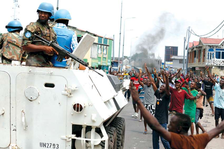 People chant slogans against Congolese President Joseph Kabila as armed UN peacekeepers watch protesters in Kinshasa. Politically-motivated attacks took place on Catholic churches in Kinshasa and area in late February, attacks Cadinal Laurent Monsengwo Pasinya calls deliberate attempts to ruin the path to peace.