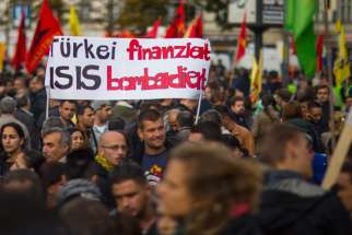 People hold a banner during an Oct. 12 demonstration in Berlin against the Islamic State militant group, known as ISIS, and its insurgent attacks on the Syrian Kurdish town of Kobani. Muslim leaders worldwide have issued a stern rebuke to ISIS.