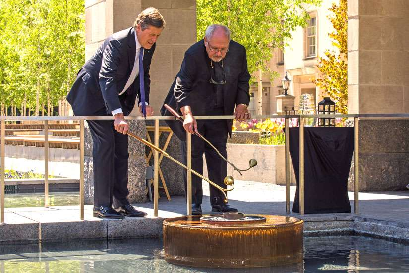 Fr. Massey Lombardi joins Toronto Mayor John Tory in relighting the eternal flame at the peace garden in Nathan Phillips Square May 18.