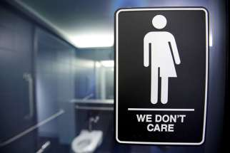A sign protesting a recent North Carolina law restricting transgender bathroom access is seen in the bathroom stalls at the 21C Museum Hotel in Durham, N.C., on May 3, 2016.