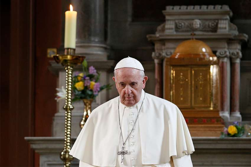 Pope Francis walks in front of a candle in memory of victims of sexual abuse as he visits St. Mary's Pro-Cathedral in Dublin Aug. 25. Pope Francis apologized for clerical sexual abuse in Ireland but on the final day of the trip, he was accused of ignoring abuse by Cardinal Theodore E. McCarrick.