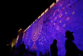 "People walk past an image of a Menorah projected on a wall surrounding the Old City of Jerusalem Dec. 8. Although Catholic are called to witness to their faith, the church ""neither conducts nor supports"" any institutional missionary initiative directed toward Jews, according to a new document from a Vatican commission."