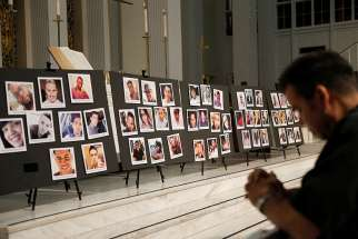 A man prays in front of photographs of victims of the Pulse nightclub shooting in Orlando June 15, 2016. The Diocese of Orlando held a prayer service on the tragedy's anniversary at St. James Cathedral June 12.