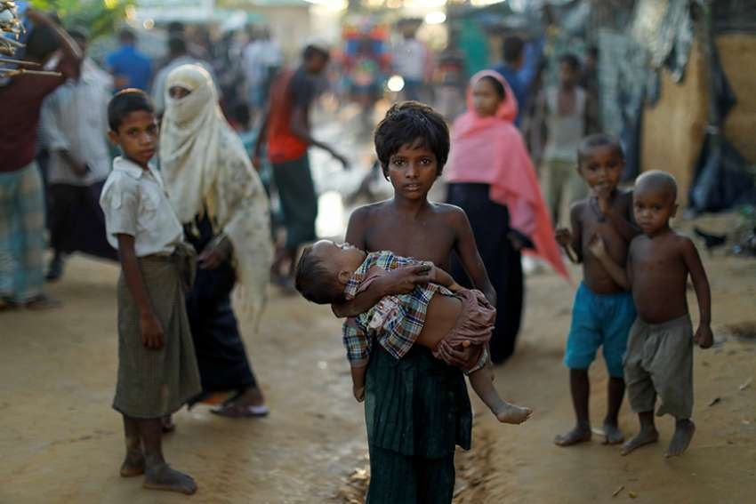 "A young Rohingya refugee carries a child Oct. 10 while walking in a camp near Cox's Bazar, Bangladesh. Pope Francis, who will visit Bangladesh Nov. 30-Dec. 2, has appealed for their protection of the Rohingya on several occasions, calling them ""our brothers and sisters."""