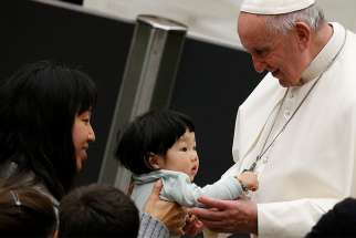 Pope Francis greets a child during his general audience in Paul VI hall at the Vatican Jan. 9.