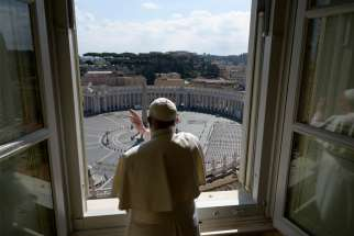 Standing in the window of the library of the Apostolic Palace overlooking an empty St. Peter's Square, Pope Francis blesses the city of Rome March 15, 2020, still under lockdown to prevent the spread of the coronavirus.