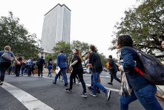 Students from Marjory Stoneman Douglas High School in Parkland, Fla., cross a street in Tallahassee prior to speaking with Florida state legislators Feb. 20 at the Capitol. About 100 students from the Parkland school traveled in a three-bus caravan to demand gun restrictions a week after the deadly shooting that left 17 of their classmates and teachers dead.