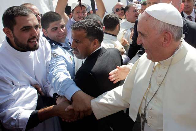 Pope Francis is greeted by pilgrims after arriving to celebrate Mass at Amman International Stadium in Jordan May 24. Celebrating Mass on his first day in the Holy Land, Pope Francis said hope for peace in a region torn by sectarian conflicts comes from faith in God.