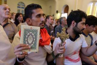 An Iraqi man carrying a cross and a Quran attends Mass at Mar Girgis Church in Baghdad July 20. Pope Francis called for prayers, dialogue, and peace, as the last Iraqi Christians flee the Iraqi city of Mosul.