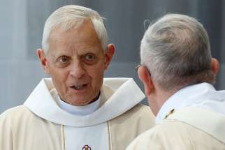 Cardinal Donald W. Wuerl of Washington prepares to exchange the sign of peace with Pope Francis as the Pope celebrates Mass in Washington Sept. 23, 2015.
