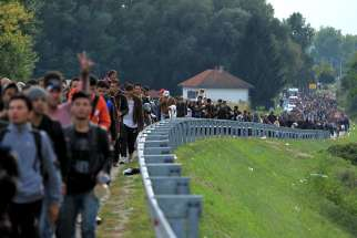 "Migrants walk toward the Hungarian border after arriving at the train station in Botovo, Croatia, Oct. 6, 2015. Hungarian lay Catholics have circulated a petition, signed by members of other denominations, urging their country's churches to stop ""closing their eyes"" to the plight of refugees."