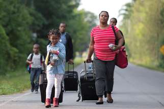A Haitian family walks to cross the U.S.-Canada border into Quebec from New York Aug. 29.