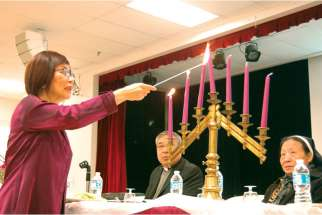 A volunteer lights the candles, as Fr. Dominic Qin watches, to begin the Passover celebrations at Chinese Martyrs parish.