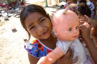 A girl at an informal refugee camp set up by Indigenous Venezuelans shows off her doll.