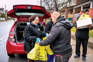 The pandemic has put a spotlight on volunteer efforts in the community. Above, Lorna Bahamondes delivers groceries on behalf of the Society of St. Vincent de Paul.