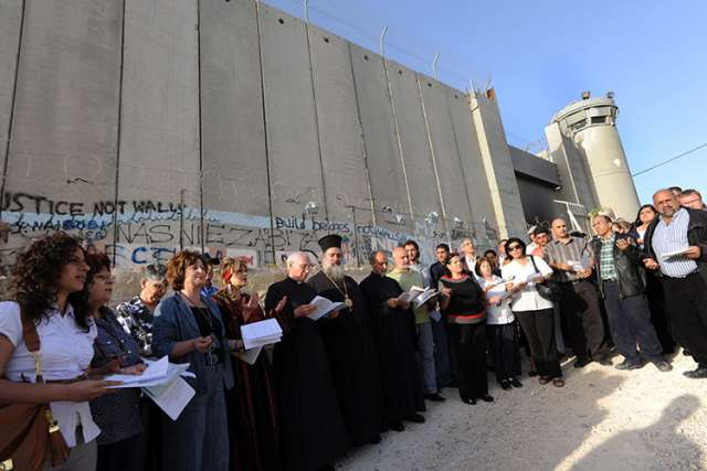 Christian leaders pray in front of the Israeli separation wall.