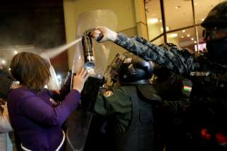 Riot police in La Paz, Bolivia, spray protesters with pepper spray Oct. 21, 2019.