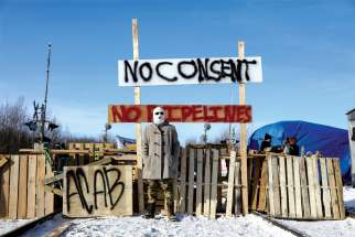 A supporter of the Wet'suwet'en Nation's hereditary chiefs poses in Edmonton Feb. 19 at a railway blockade as part of protests against British Columbia's Coastal GasLink pipeline.