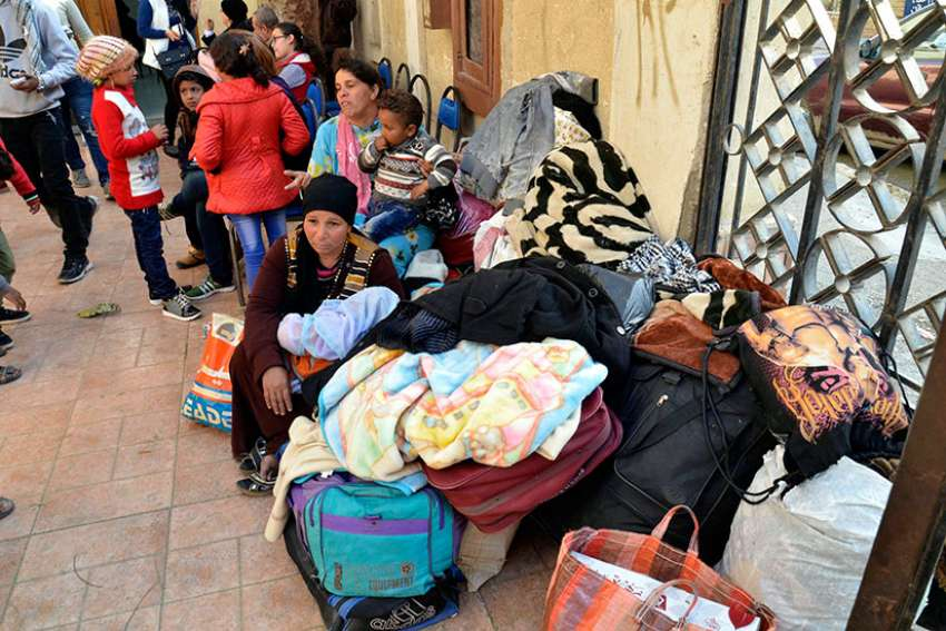 Displaced Egyptian Christian families, who used to live in the north of the Sinai Peninsula, sit near their belongings after arriving Feb. 24 at a church in Ismailia. Catholic churches in Ismailia, with help from Caritas, have helped Coptic Orthodox fleeing Islamic State attacks in North Sinai.