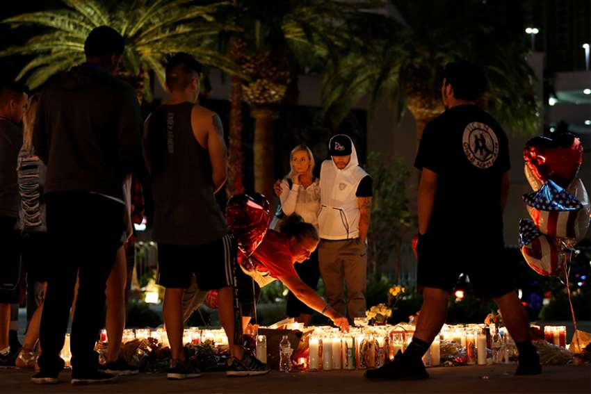 People comfort each other during an interfaith memorial for mass shooting victims led by Bishop Joseph Pepe of Las Vegas, the evening of Oct. 2.