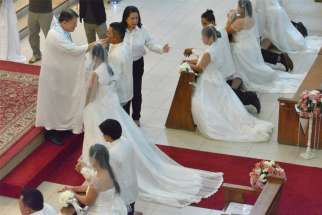 Couples receive Communion during a mass wedding in 2015 at St. Alphonsus Mary de Ligouri Church in Makati City, Philippines. A Philippine Catholic official expressed surprise over the speedy acceptance of legislation that would legalize divorce in the Philippines.